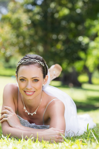Beautiful young bride relaxing on grassの写真素材 [FYI00000734]
