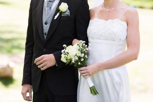 Newlywed couple holding hands in gardenの写真素材 [FYI00000738]