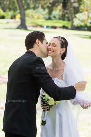 Groom kissing bride in gardenの写真素材 [FYI00000745]
