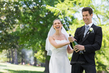 Newlywed couple popping cork of champagneの写真素材 [FYI00000747]