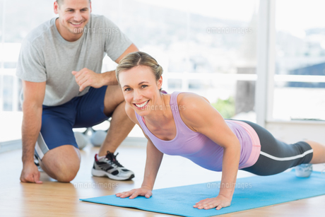 Woman doing push ups with trainerの写真素材 [FYI00000748]