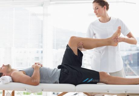 Physiotherapist massaging leg of manの写真素材 [FYI00000752]
