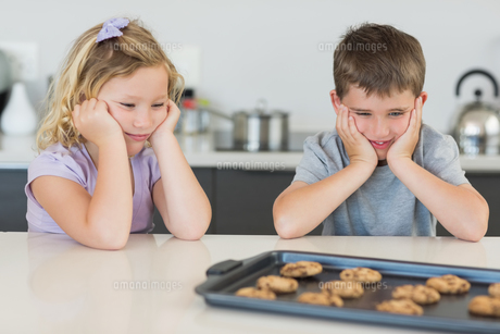 Brother and sister looking at tempting cookiesの写真素材 [FYI00000754]