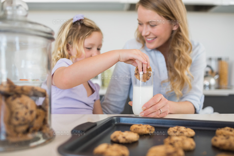 Woman with daughter dipping cookie in milkの素材 [FYI00000758]