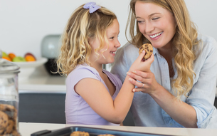 Girl feeding cookie to mother in kitchenの写真素材 [FYI00000762]