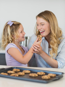 Girl feeding cookie to motherの写真素材 [FYI00000763]