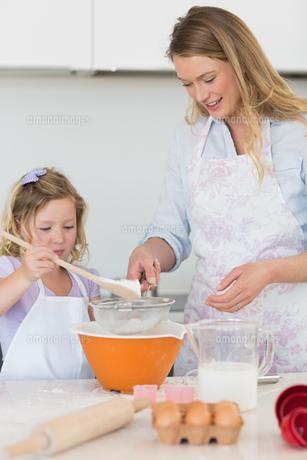 Mother teaching daughter to make cookiesの写真素材 [FYI00000764]