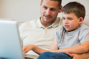 Father assisting boy in using laptopの写真素材 [FYI00000767]