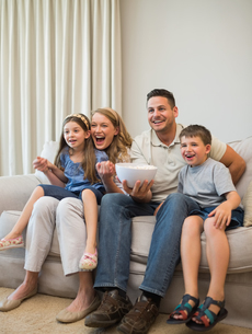 Excited family watching television on sofaの写真素材 [FYI00000769]