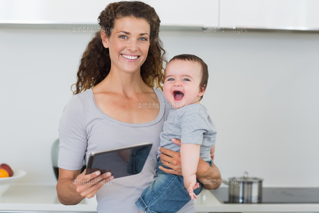 Happy mother with tablet carrying cheerful babyの素材 [FYI00000774]