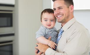 Happy businessman carrying babyの写真素材 [FYI00000776]