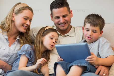Family using digital tablet together on sofaの写真素材 [FYI00000785]