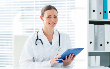 Happy female doctor holding digital tabletの写真素材 [FYI00000804]
