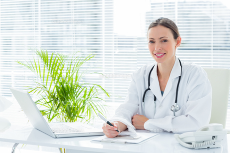 Smiling doctor at desk in clinicの写真素材 [FYI00000806]