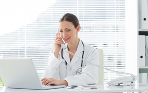 Doctor using land line phone and laptopの写真素材 [FYI00000808]