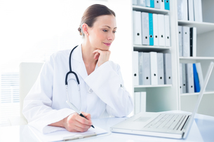 Doctor writing while using laptopの写真素材 [FYI00000811]