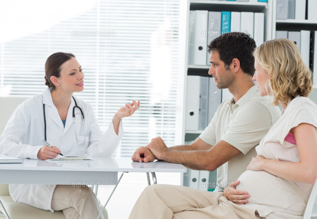 Dynaecologist discussing with expectant coupleの素材 [FYI00000814]