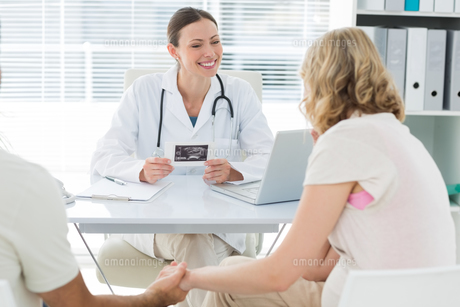 Gynaecologist talking to expectant coupleの写真素材 [FYI00000822]