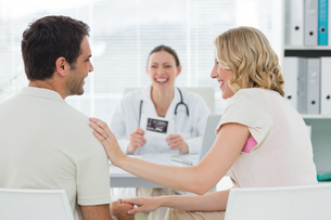 Expectant couple with doctor in clinicの写真素材 [FYI00000823]