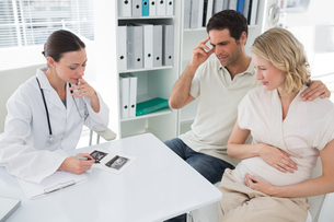 Expectant couple and doctor discussing over reportsの写真素材 [FYI00000825]