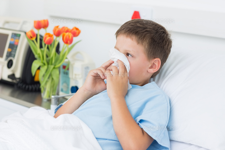 Boy blowing nose into tissue in hospitalの写真素材 [FYI00000855]