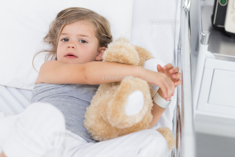 Cute girl hugging teddy bear in hospital bedの写真素材 [FYI00000858]