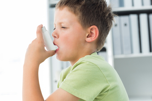 Boy using an asthma inhaler in clinicの写真素材 [FYI00000872]