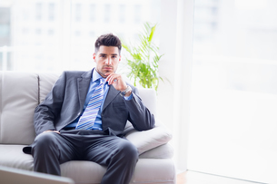 Serious businessman sitting on the sofa looking at cameraの写真素材 [FYI00000884]