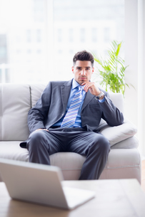Serious businessman sitting on the couch looking at cameraの写真素材 [FYI00000892]