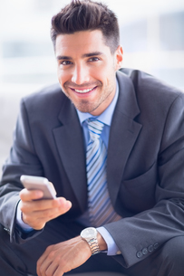 Happy businessman sitting on sofa sending a textの写真素材 [FYI00000895]