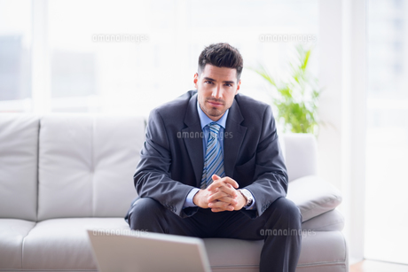 Happy businessman sitting on the sofa looking at cameraの素材 [FYI00000896]