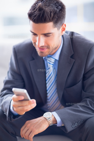 Businessman sitting on sofa sending a textの素材 [FYI00000898]
