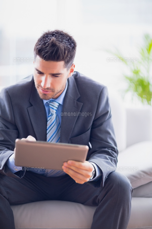 Businessman sitting on sofa using his tablet pcの素材 [FYI00000901]
