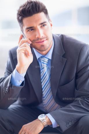 Happy businessman sitting on sofa making a callの写真素材 [FYI00000902]
