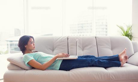 Young girl lying on sofa using her laptopの写真素材 [FYI00000904]