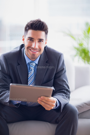 Businessman sitting on sofa using his tablet pc smiling at cameraの素材 [FYI00000908]