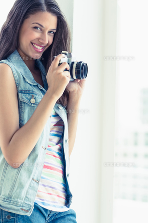 Stylish young woman taking a photo smiling at cameraの写真素材 [FYI00000909]