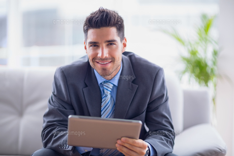 Businessman sitting on sofa using his tablet smiling at cameraの写真素材 [FYI00000910]