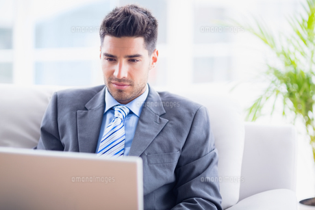 Young businessman sitting on couch using his laptopの素材 [FYI00000911]