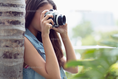 Young girl taking photographs outsideの写真素材 [FYI00000917]