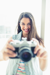 Smiling young woman taking a photo at cameraの写真素材 [FYI00000918]