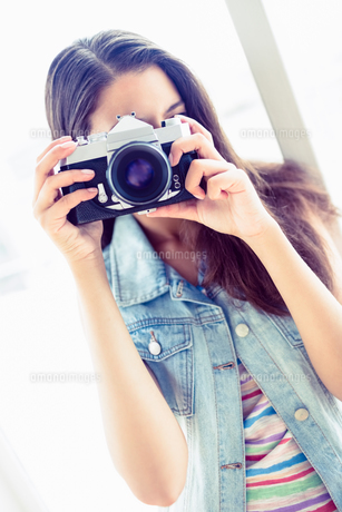 Smiling young woman taking a photoの写真素材 [FYI00000920]