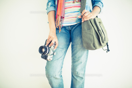 Woman in jeans holding camera and shoulder bagの写真素材 [FYI00000926]