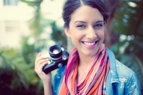 Cheerful brunette photographer standing outside smiling at cameraの素材 [FYI00000931]