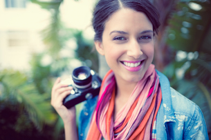 Cheerful brunette photographer standing outside smiling at cameraの写真素材 [FYI00000931]