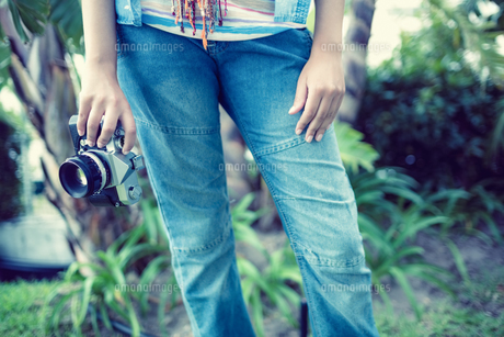 Woman wearing jeans holding camera outsideの素材 [FYI00000934]