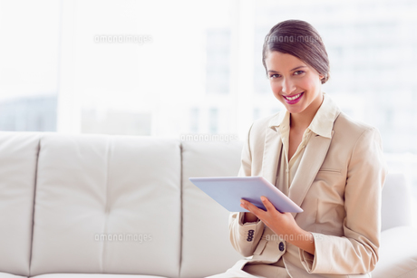 Stylish businesswoman sitting on sofa using tablet smiling at cameraの素材 [FYI00000938]