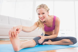 Toned blonde stretching on exercise mat smiling at cameraの写真素材 [FYI00000940]