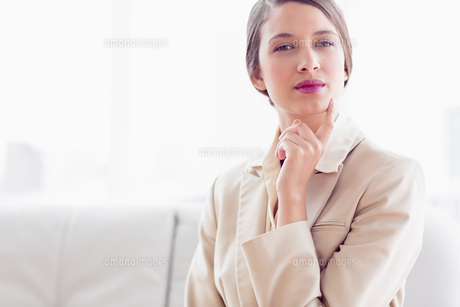 Young thinking businesswoman sitting on sofa looking at cameraの写真素材 [FYI00000942]