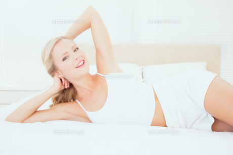 Sexy young blonde lying on her bed smiling at cameraの写真素材 [FYI00000944]
